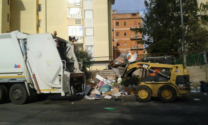 Operai Ased al lavoro per smaltire l'accumulo di rifiuti